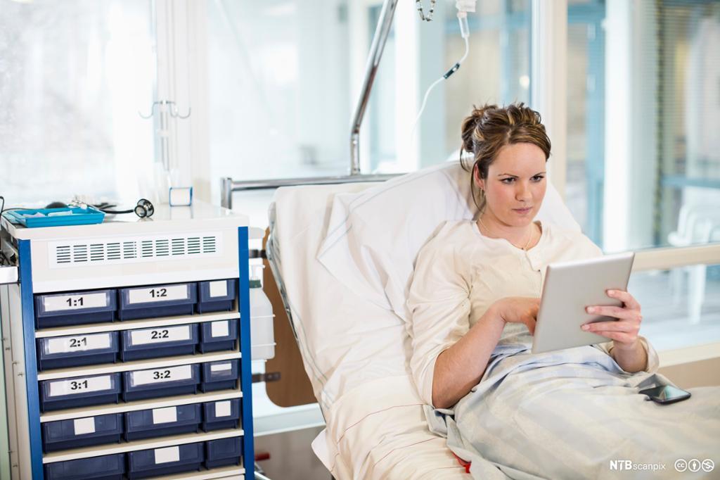Ung kvinne leser på nettbrett mens hun ligger i sykehusseng. Foto.