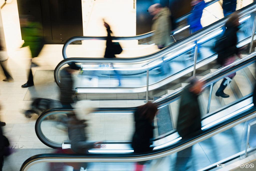 Utydelig bilde av en rekke mennesker i rulletrapper. Foto.
