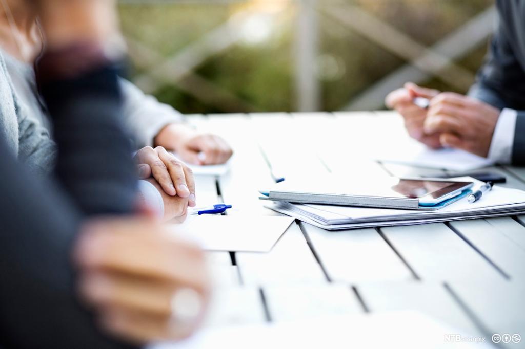 Personer rundt et bord med notater og brett foran seg. Vi ser bare hendene og bordet. Foto.