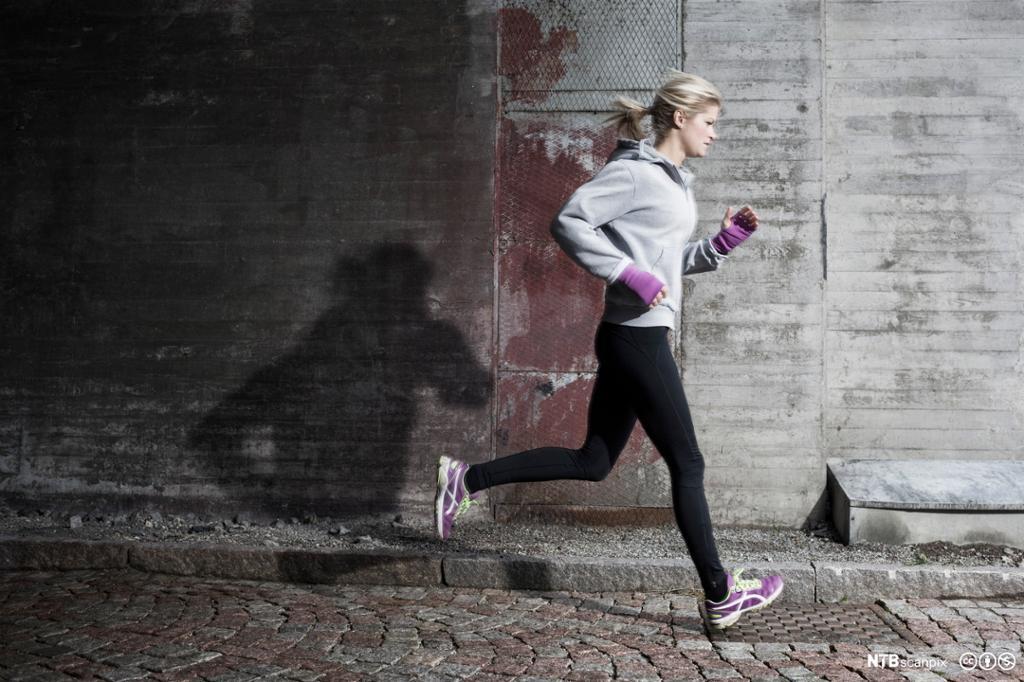 Kvinne jogger på gata. Foto.