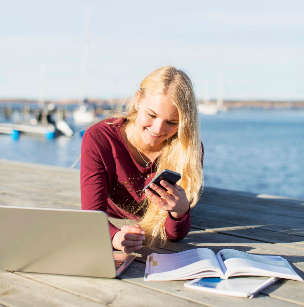 Jente ligger på magen og ser på mobil, PC og bok. Foto.