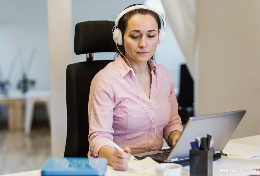 Kvinne med hodesett foran datamaskin. Foto.