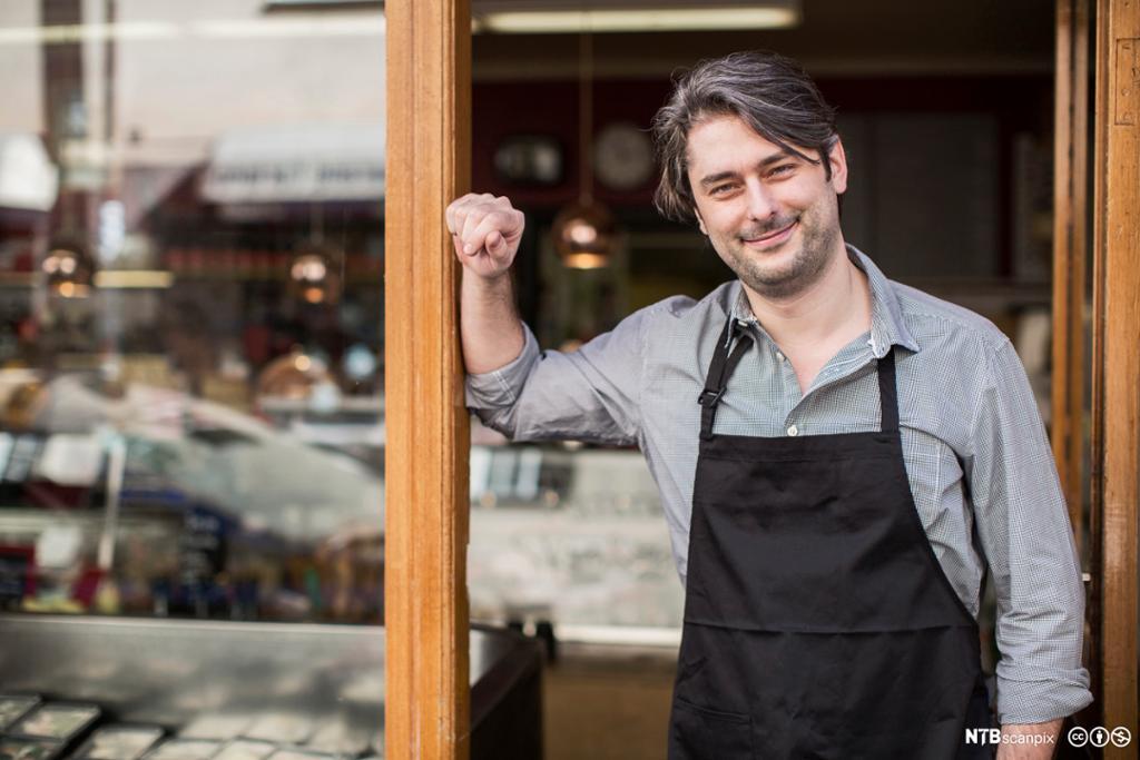 Smilende servitør i åpen inngangsdør. foto.