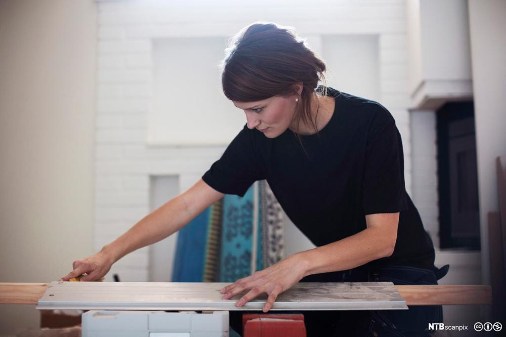 Ung kvinnelig snekker som måler opp en planke. Foto.