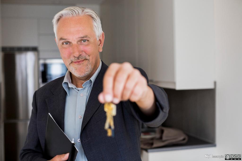 En mann holder frem et nøkkelknippe. Foto.