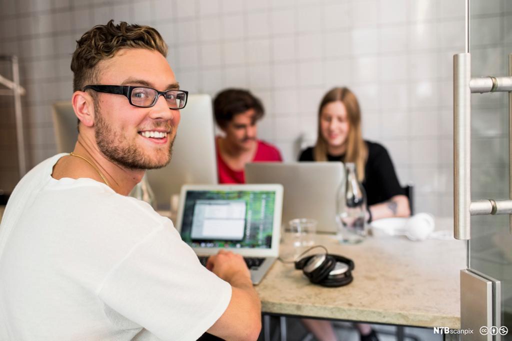 Ung mann sitter foran datamaskin i kontorfellesskap. Foto.