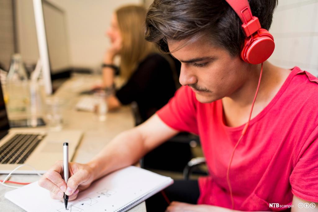 Ung mann jobber med skriftlig vurdering. Foto.