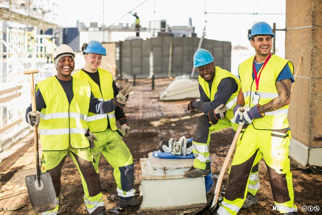 Glade bygningsarbeidere på arbeidsplass. Foto
