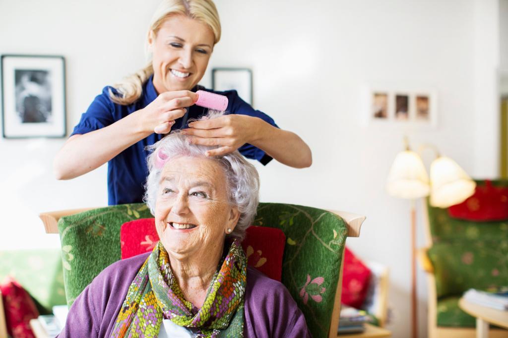 Helsefagarbeider hjelper pasient med hårpleie. Foto.