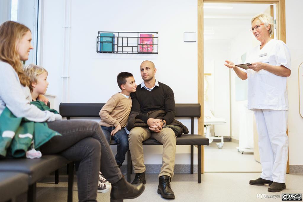 Helsepersonell snakker med to som sitter på venterommet. Foto.
