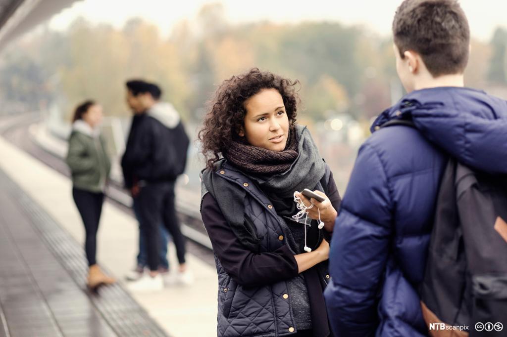 Multietnisk ungdom i samtale på togplattform. Foto.