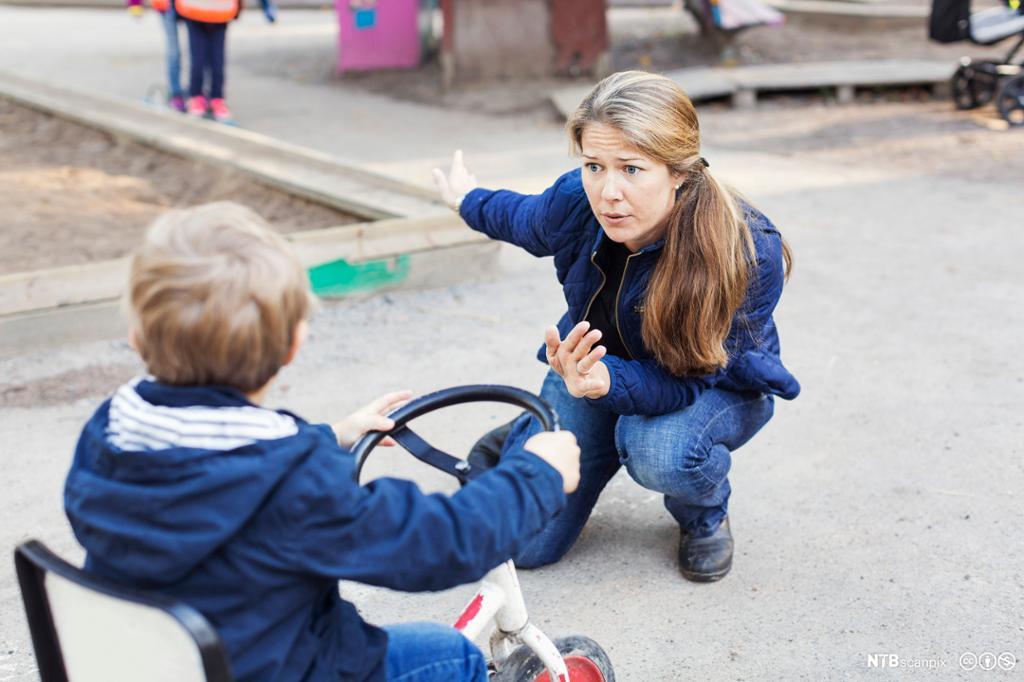 Sint voksen på et barn på trehjulssykkel. Bilde.