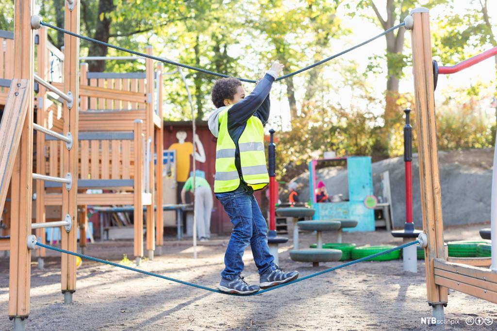 Gutt balanserer i tau på lekeplass. foto.