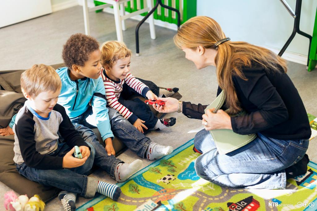 Voksen veileder barn i barnehagen. Bilde.