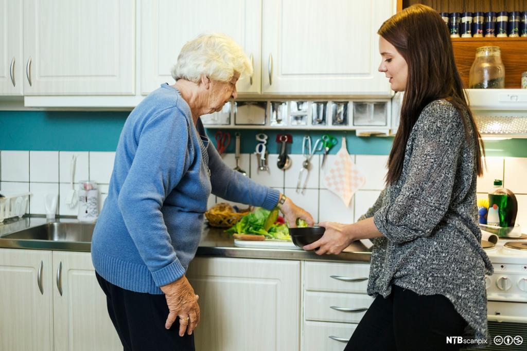 Eldre dame som får hjelp til å koke kaffe. Foto