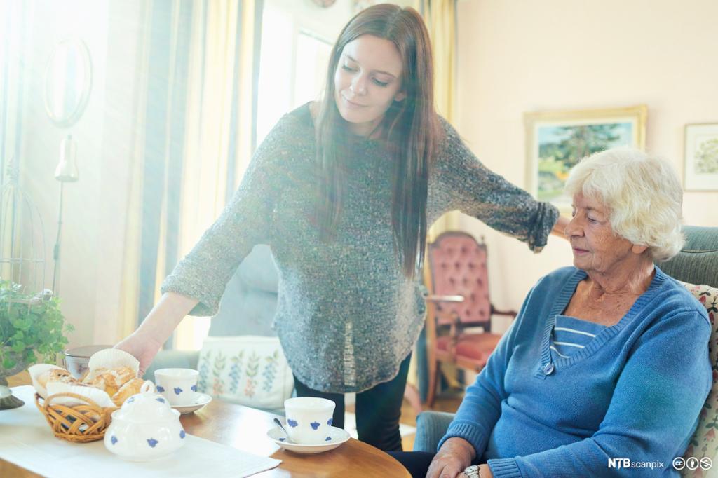 Ei eldre dame blir servert av ein sjukepleiar.