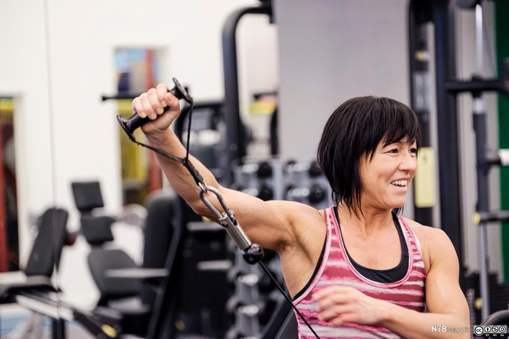 Kvinne trener styrke på et treningssenter.