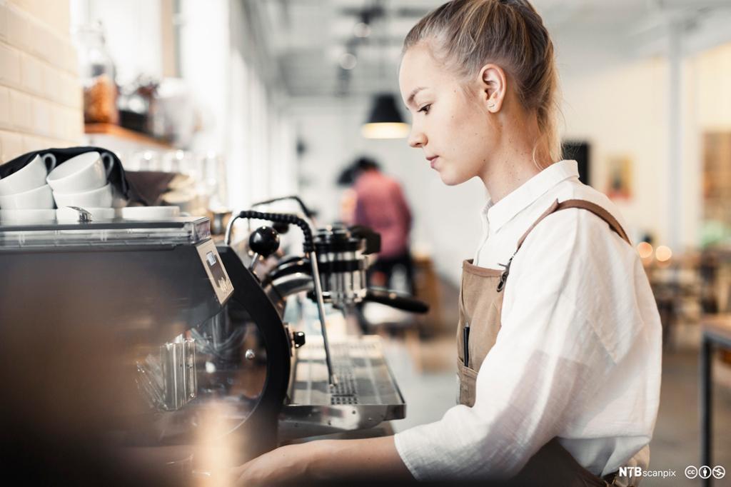 Ung person ved kaffemaskin. Foto.