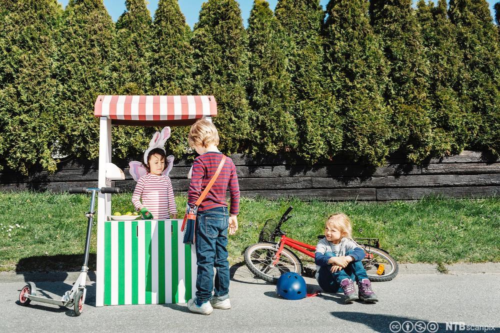 Barn selger saft fra saftbod. Foto.