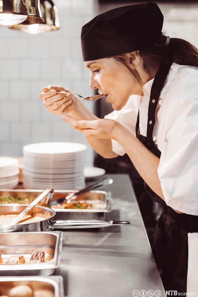 En kvinnelig kokk smaker på maten med en skje. Foto.