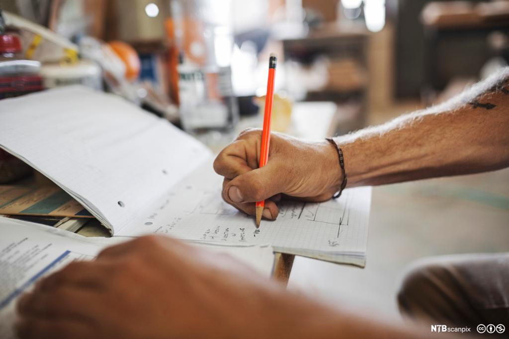 Snekker skriver med blyant på blokk. Bilde.