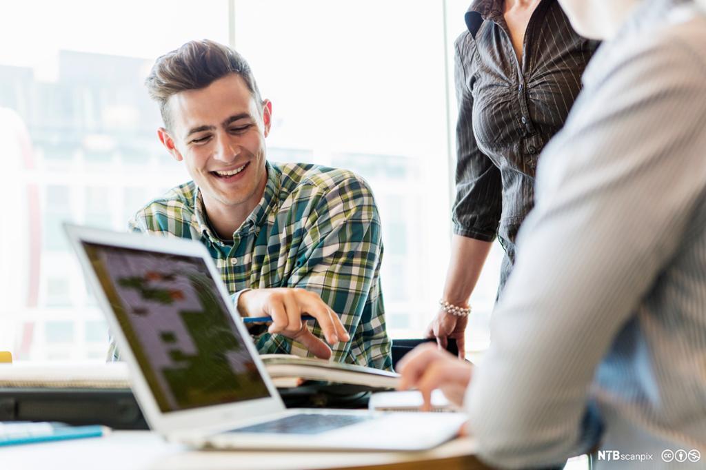 En IKT-servicemedarbeider hjelper en bruker. Foto.