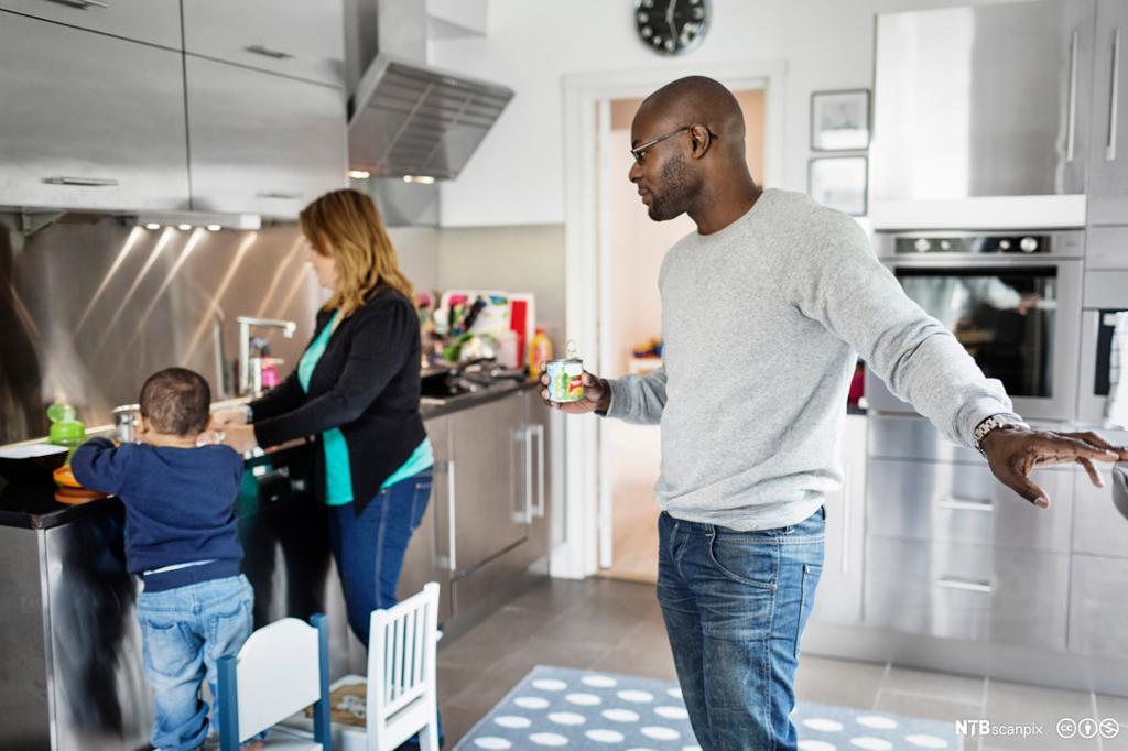 Mann ser på mor og sønn forbereder mat på kjøkkenet. Foto.