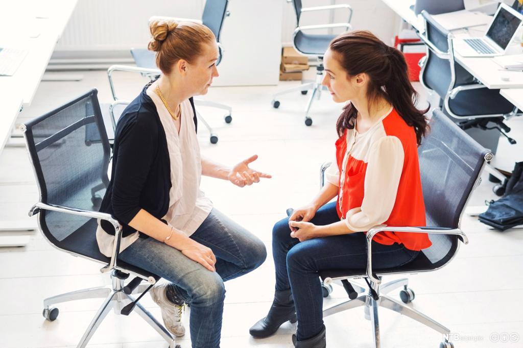 En forretningskvinne har diskusjon med kvinnelig kollega på kontoret. Foto.