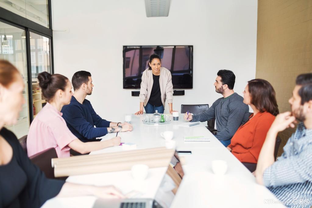 Et jobbmøte. Ved enden av et langt bord står en kvinne. Hun leder møtet. De seks andre møtedeltakerne sitter henholdsvis til venstre og til høyre for henne. Foto.