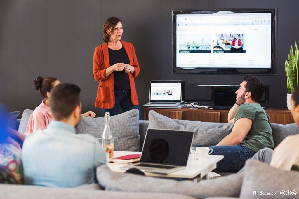 Forretningskvinne holder presentasjon for kollegaer. Foto.