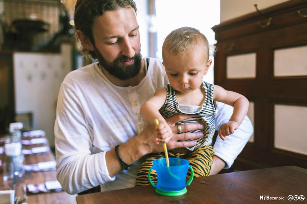 Mann med liten sønn på restaurant. Foto.