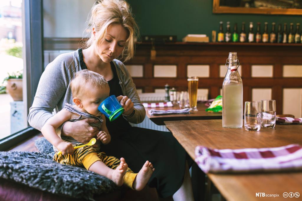 Dame hjelper lite barn å drikke på restaurant. foto.