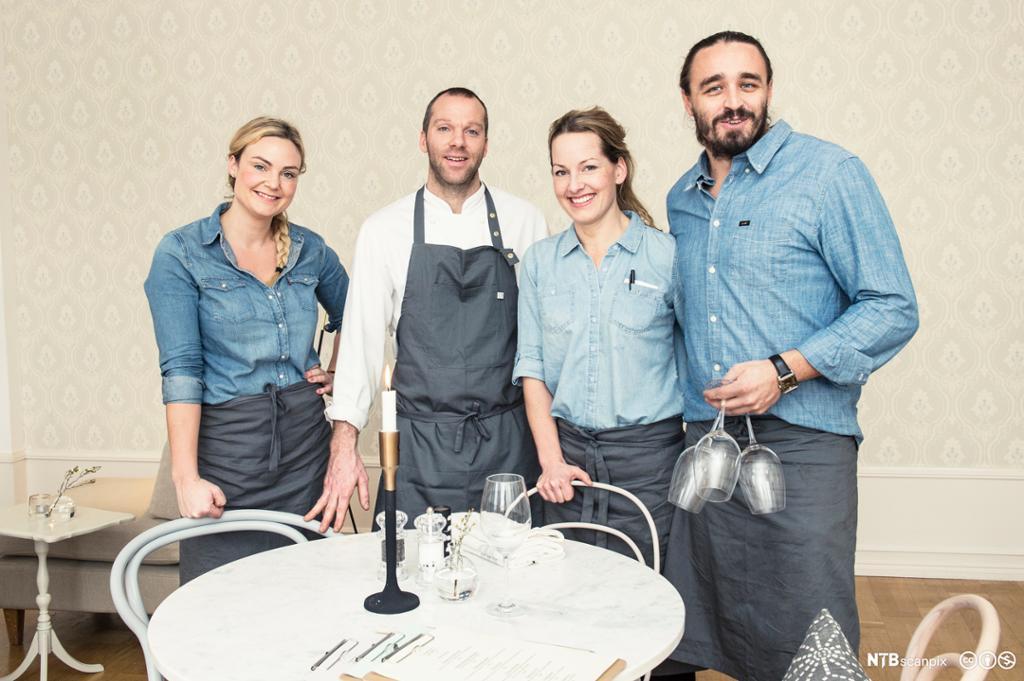 Fire ansatta i uformell uniform står ved bord i restaurant.foto.