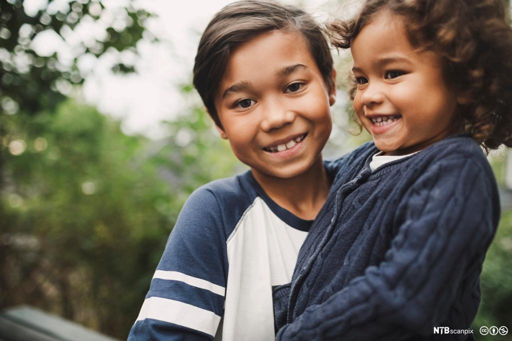 Smilende storebror bærer lillesøster. Foto.