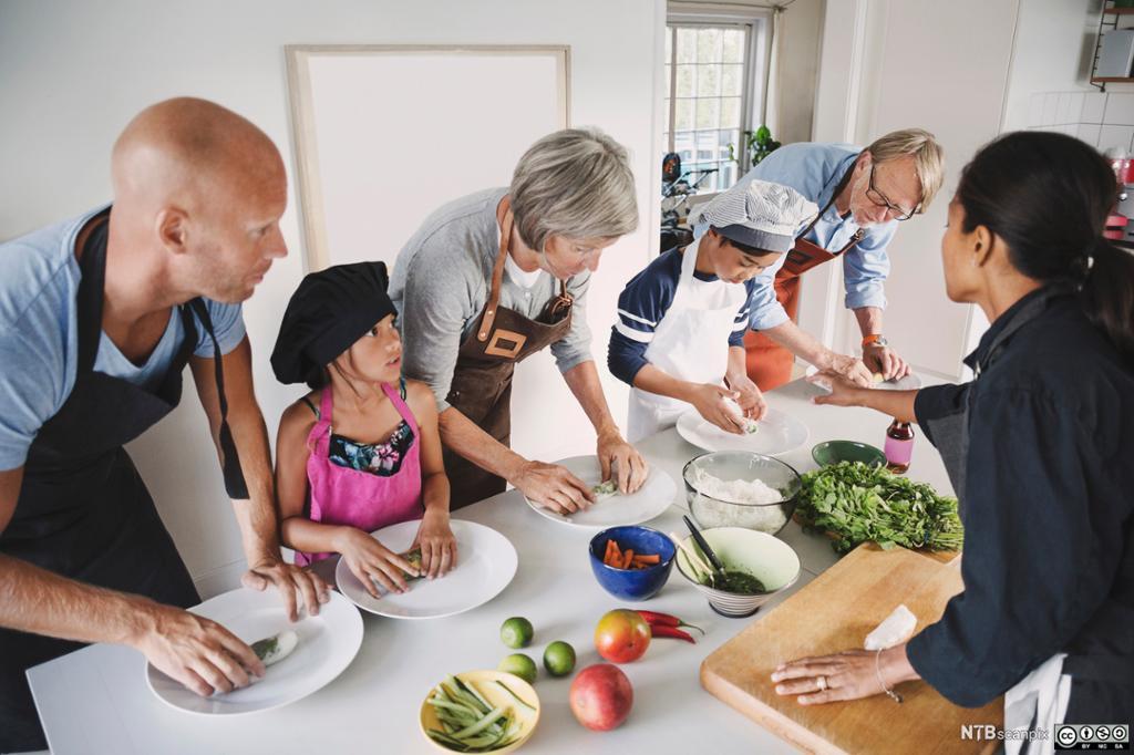 En familie lager mat sammen på kjøkkenet. Foto.