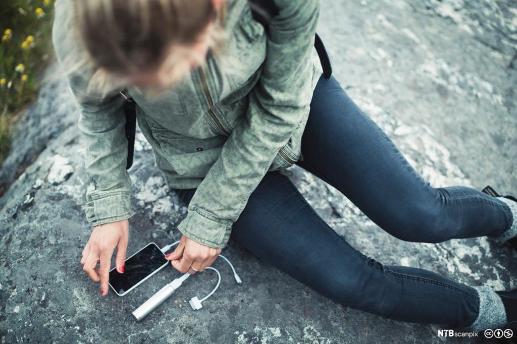 Kvinne kobler bærbar lader til mobiltelefon. Foto.