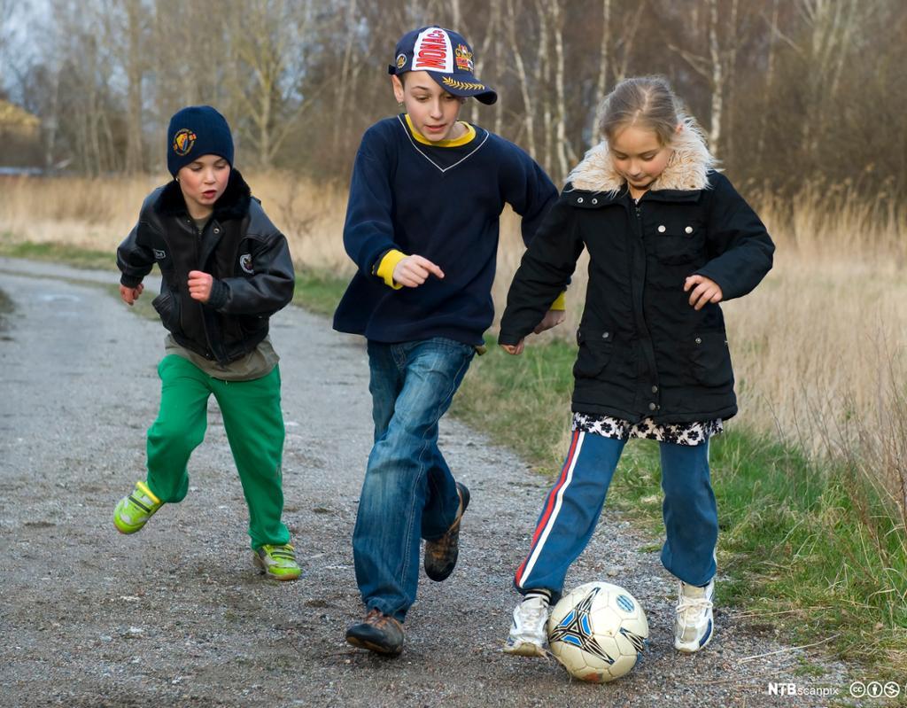 Tre barn leker med en fotball. Foto.