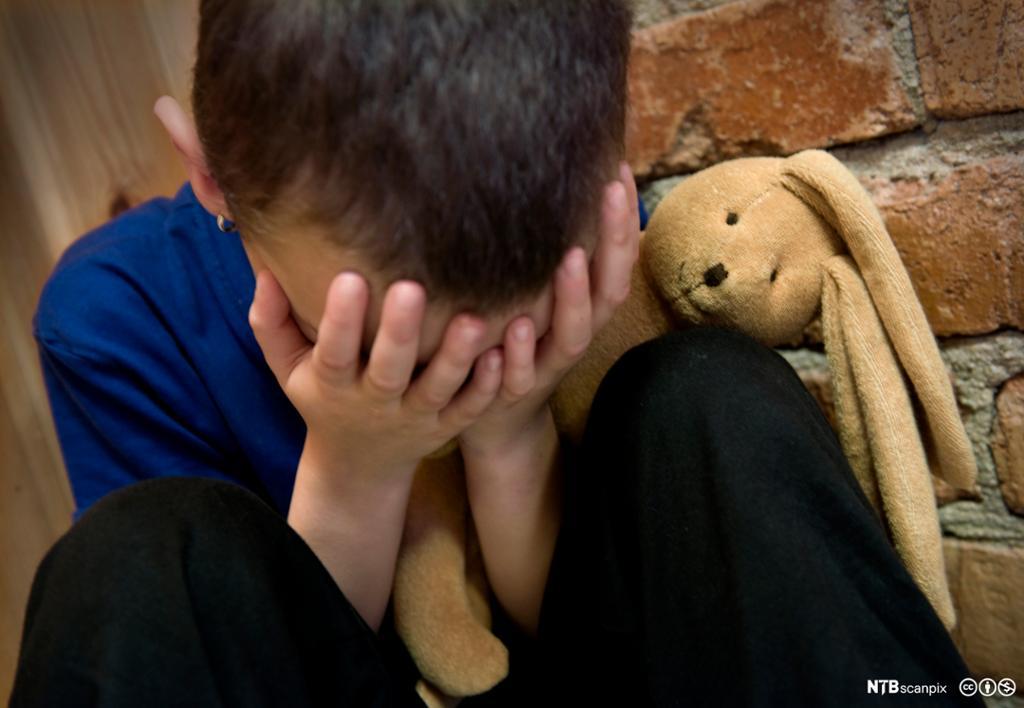 Liten gutt sitter og ser ned med hendene foran ansiktet. Foto