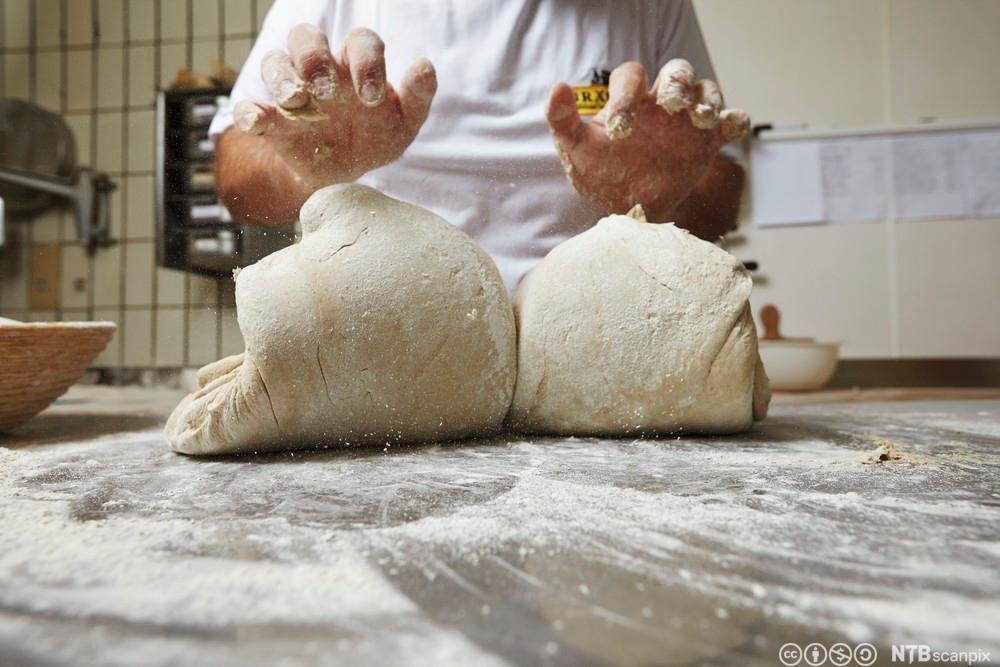 """Baker som strammer/""""verker"""" en deig. Foto."""