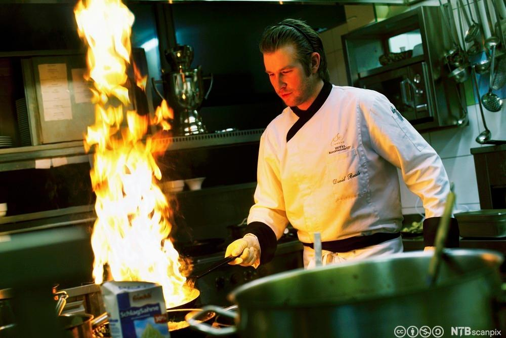 Restaurantkokk med brennende stekepanne. Foto.
