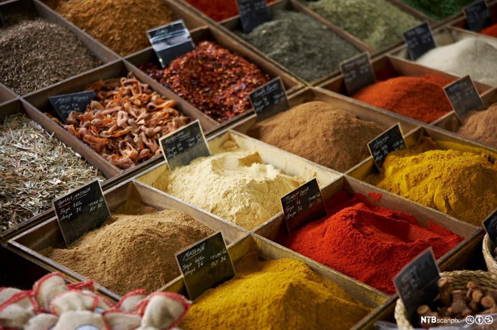Fargerike krydder i trekasser. Foto.