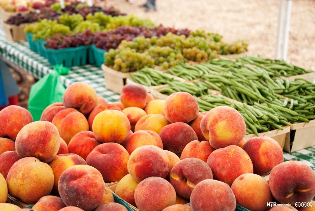 Bord med korger med fersken i forgrunnen og korger med druer og brekkbønner i bakgrunnen. Foto.
