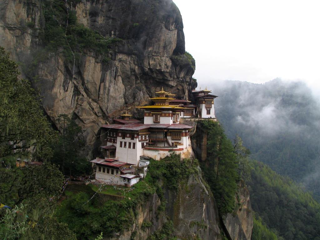 En rekke hvite hus med orientalske tak på en kippe i en bratt fjellvegg. Foto.