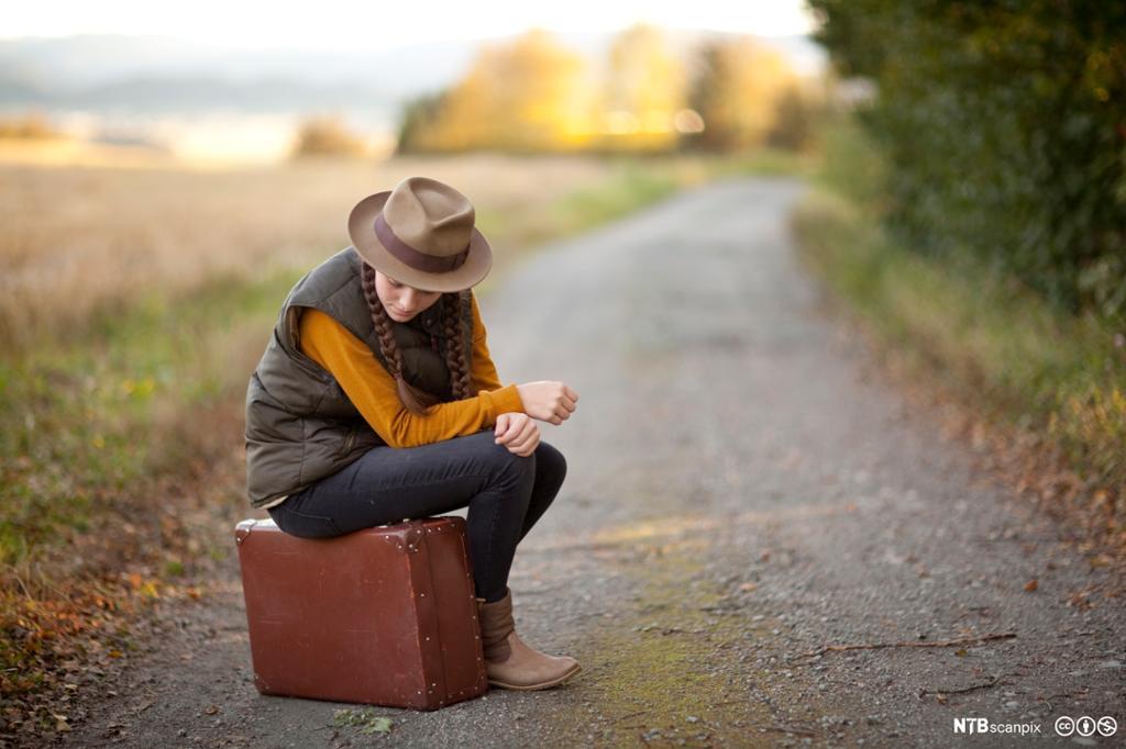 Ung kvinne sitter på en brun koffert. Grusvei. Foto.