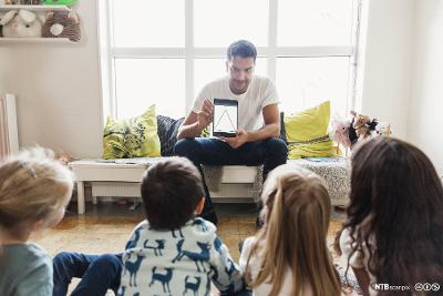 Barnehageansatt viser figur på iPad til en barnegruppe. Foto.