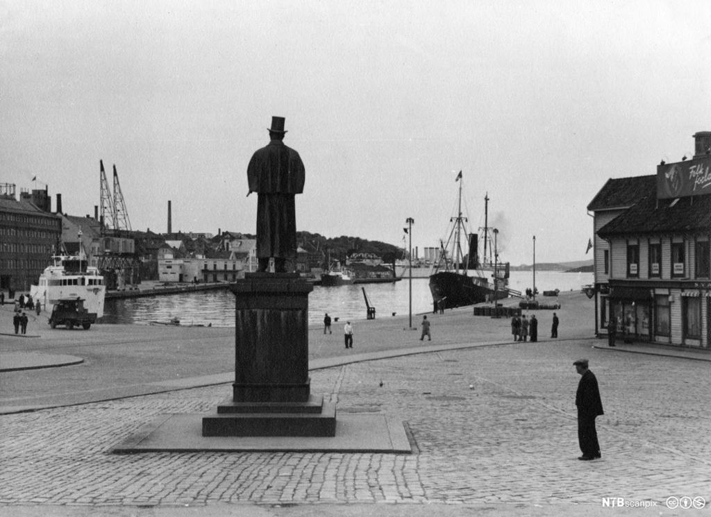 Mann på sokkel skuer ut over vågen i Stavanger. Foto.