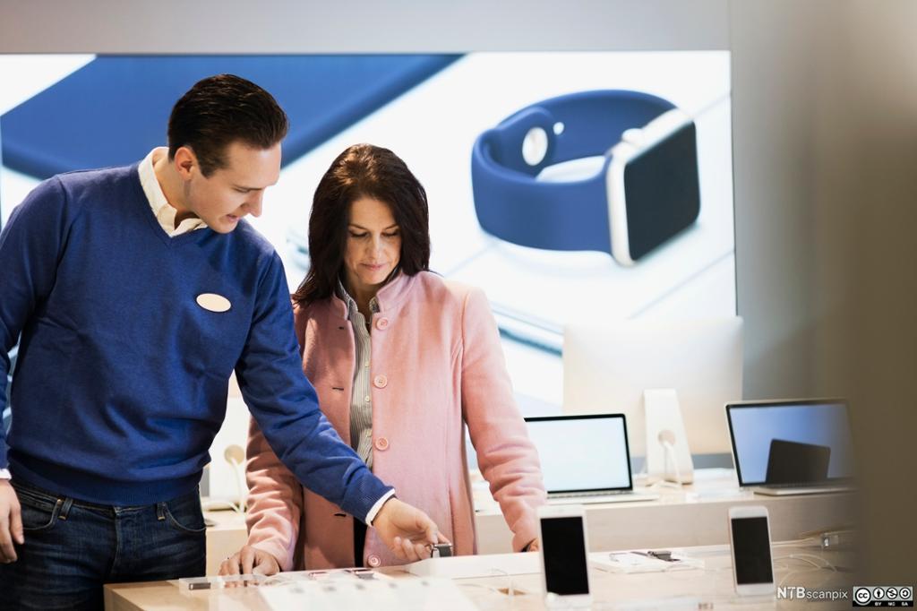En selger hjelper en kunde med å velge smarttelefon. Foto.