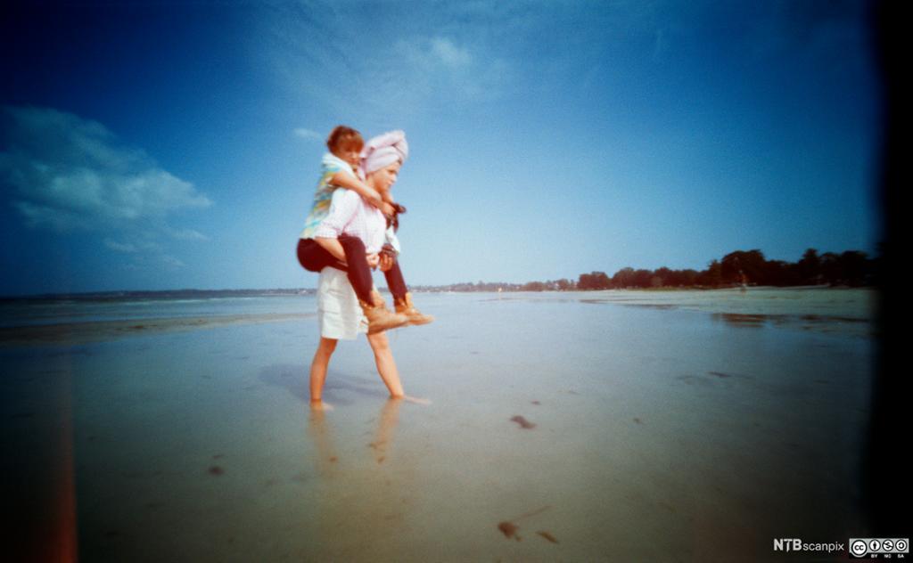 Ei jente bærer ei anna jente på stranda. Foto.