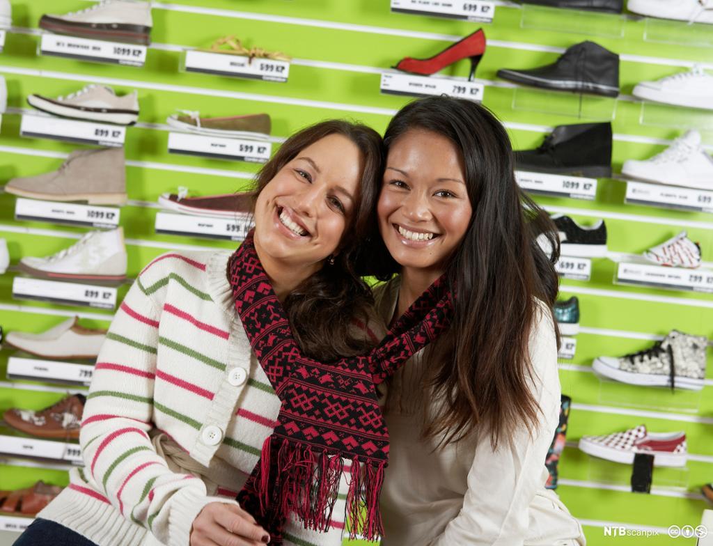 To smilende tenåringsjenter bundet sammen med et skjerf. Foto.