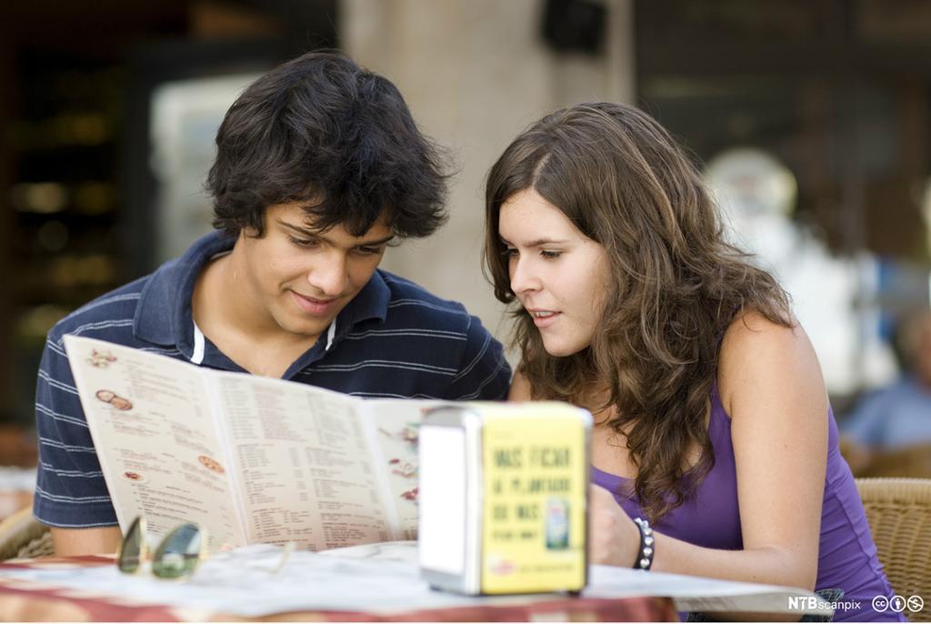 Par som leser en meny. Foto.